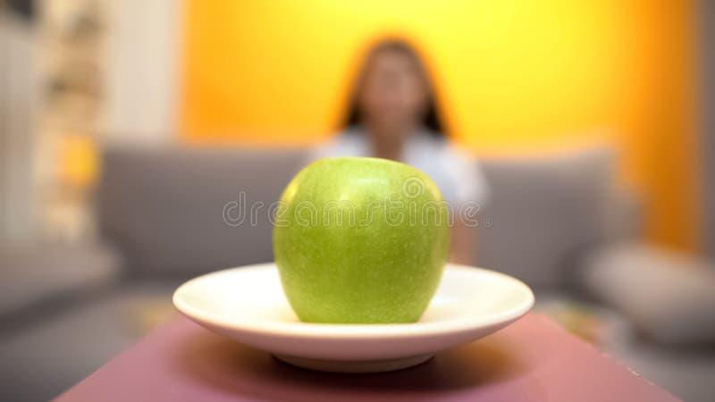 Manzana verde que miente en la placa, mujer en el fondo, dieta de agotamiento del vegano, adelgazando fotografía de archivo
