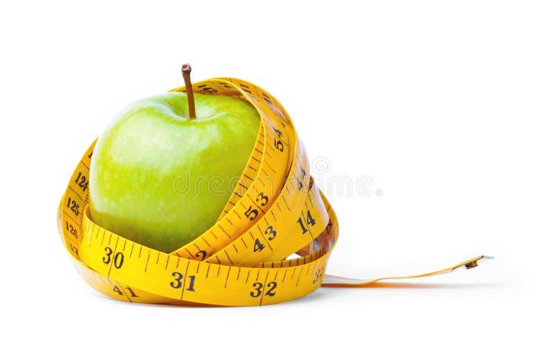 Manzana verde y cinta de medición imagen de archivo