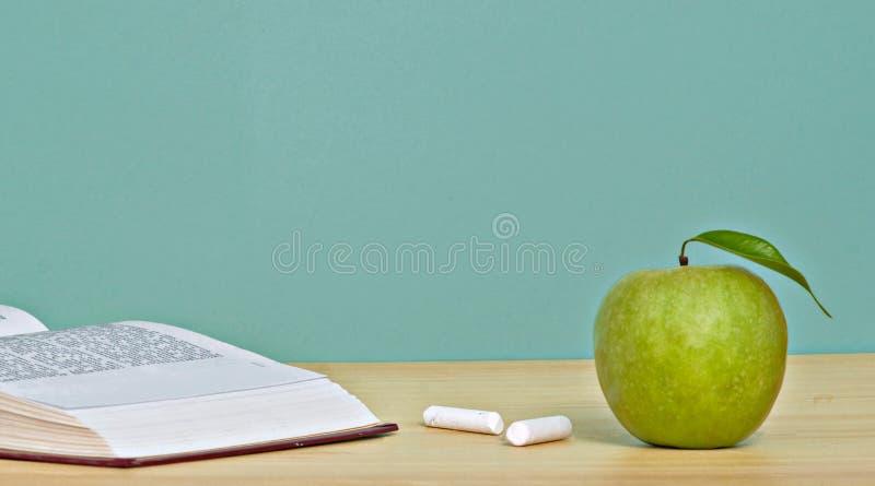 Manzana verde y libro abierto foto de archivo