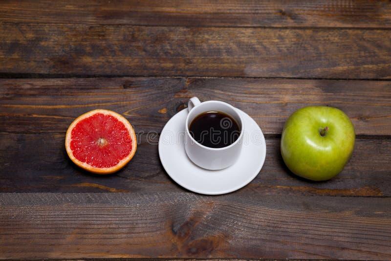 Manzana y café frescos verdes en la taza blanca con el pomelo cortado fotografía de archivo
