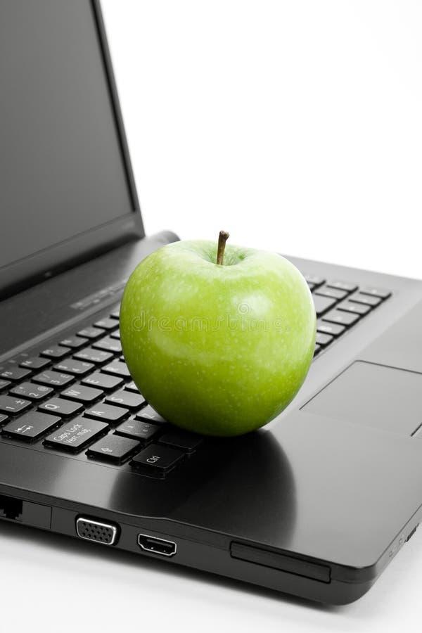 Manzana y computadora portátil verdes imagen de archivo libre de regalías