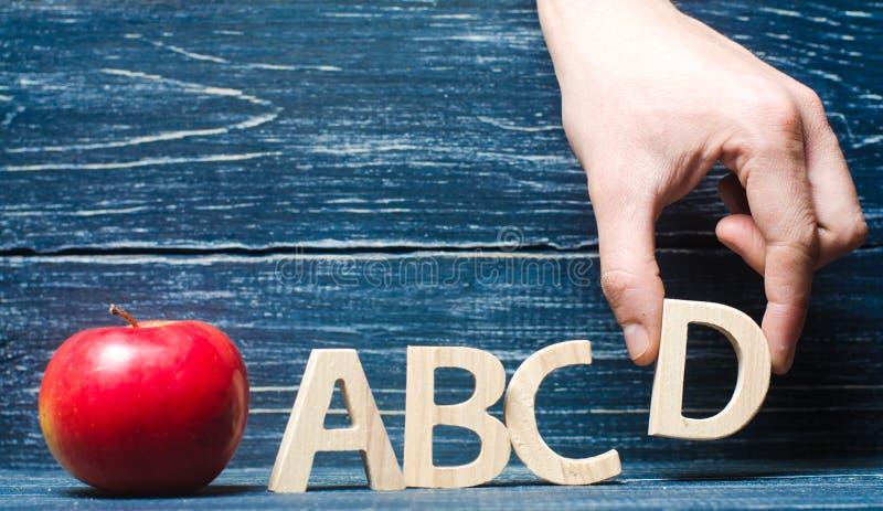 Manzana y letras rojas ABCD La mano pone la letra D en el al foto de archivo