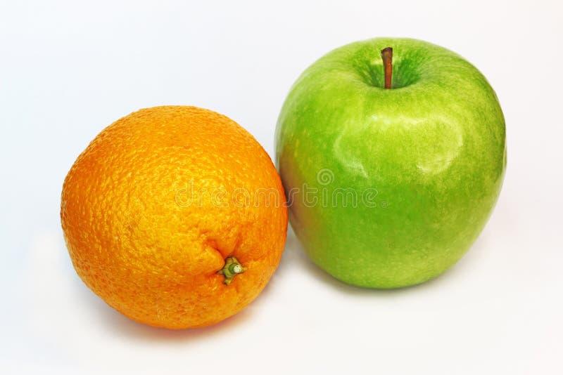 Manzana y naranja verdes imagenes de archivo