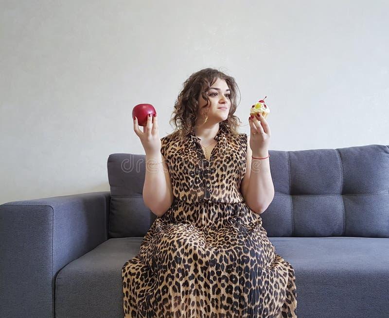 Manzana y torta llenas hermosas, sofá bien escogido del pelo rizado de la muchacha de la emoción de la expresión bonita foto de archivo