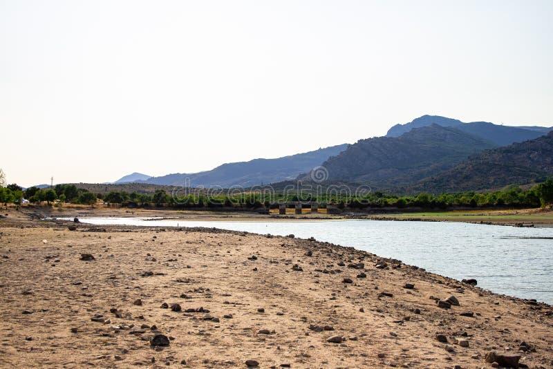 Manzanares el Real-Reservoir mit einer Brücke und Bergen im Hintergrund lizenzfreies stockbild