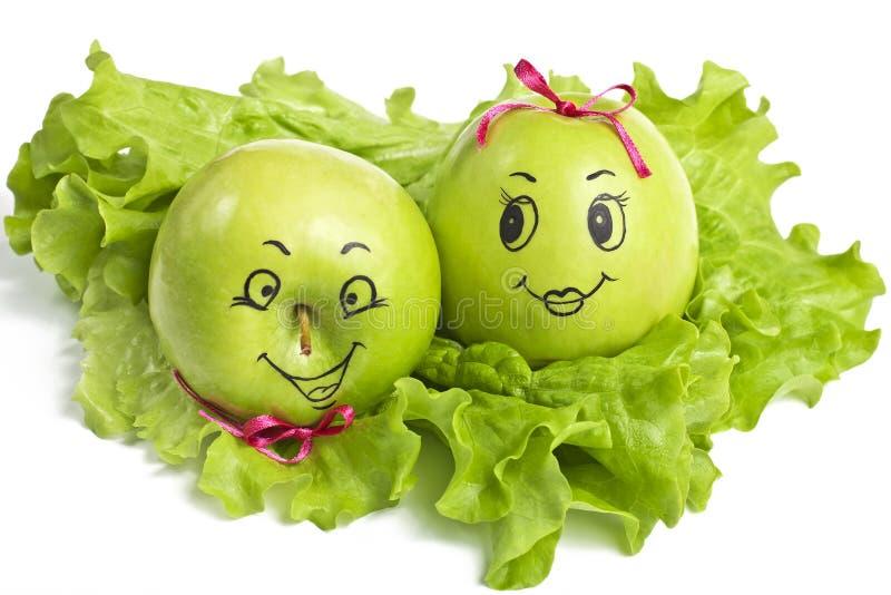 Manzanas con las caras cómicamente pintadas imagen de archivo libre de regalías