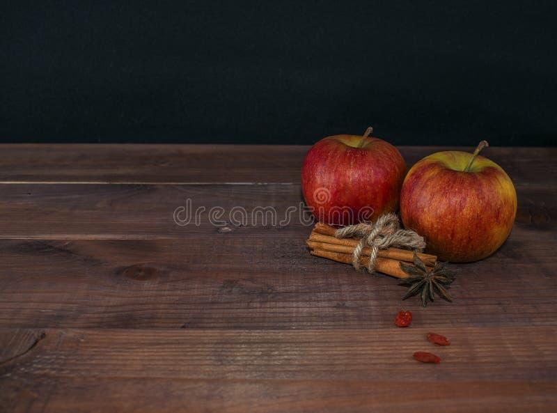 Manzanas con las especias y cinnamonon en un fondo de madera Dieta apropiada Dieta sana vegetarianism Desayuno apropiado la derec imagenes de archivo