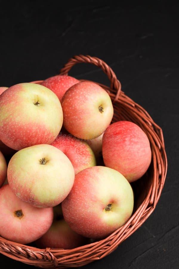 Manzanas crudas maduras en cesta de mimbre en fondo negro con el espacio de la copia - frutas amarillas y rojas orgánicas foto de archivo