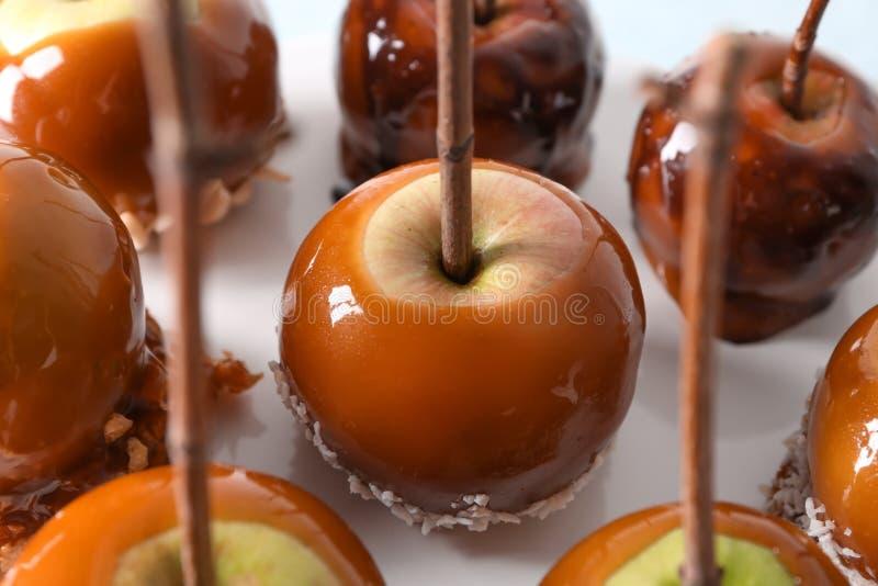 Manzanas de caramelo deliciosas con las ramas de árbol en el soporte, primer imagen de archivo libre de regalías