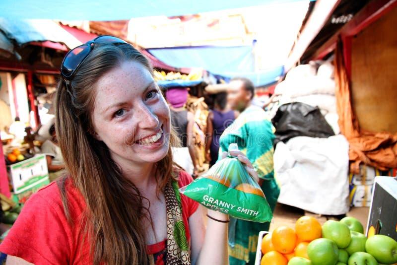 Manzanas de compra de la mujer joven en el mercado fotos de archivo