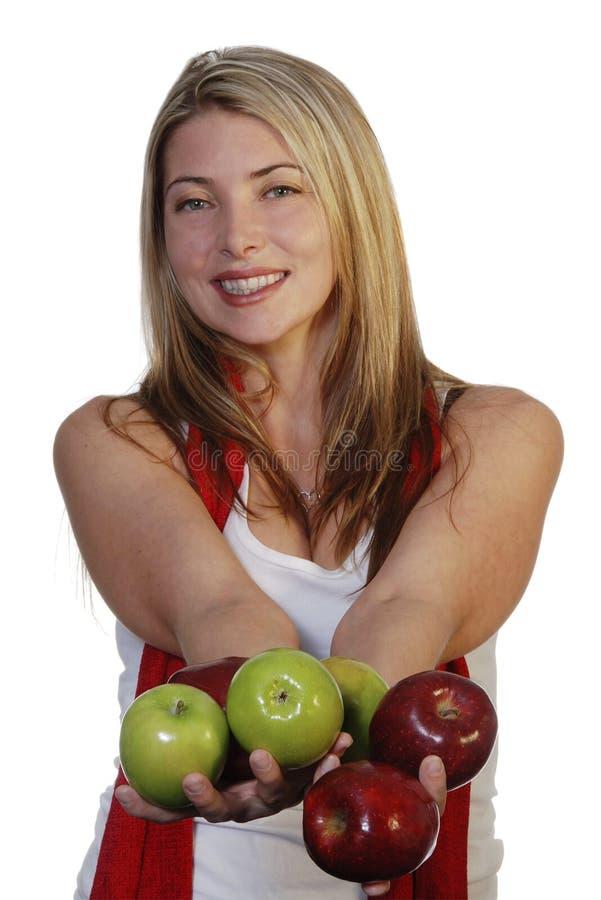Manzanas de ofrecimiento sonrientes de la mujer fotos de archivo