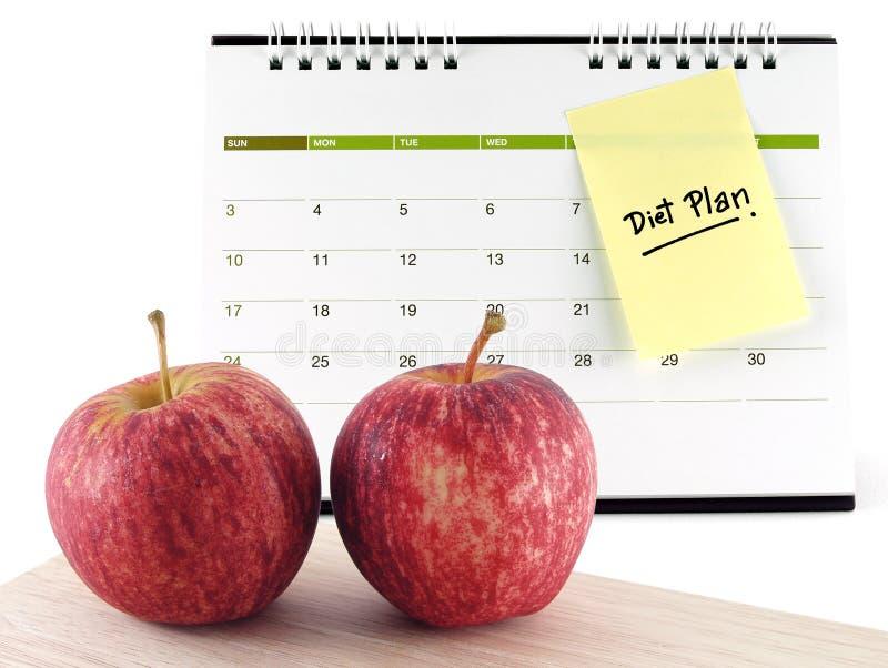 Manzanas del primer dos con la gotita en el palillo de madera de la nota del mensaje del recordatorio del plan de la tabla de cor foto de archivo