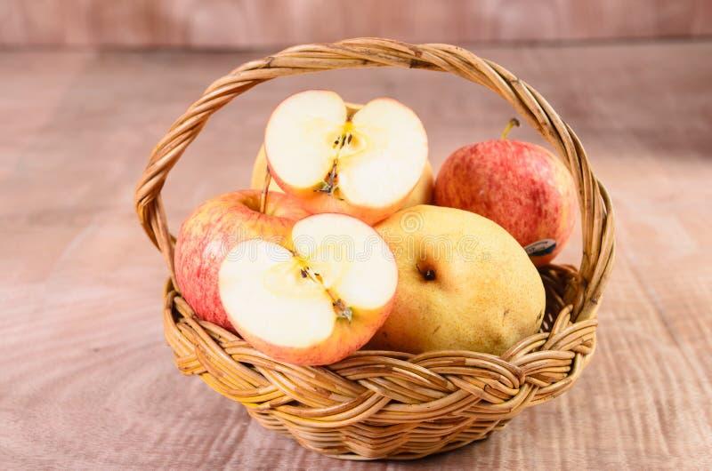 Manzanas en cesta en el fondo de madera fotos de archivo