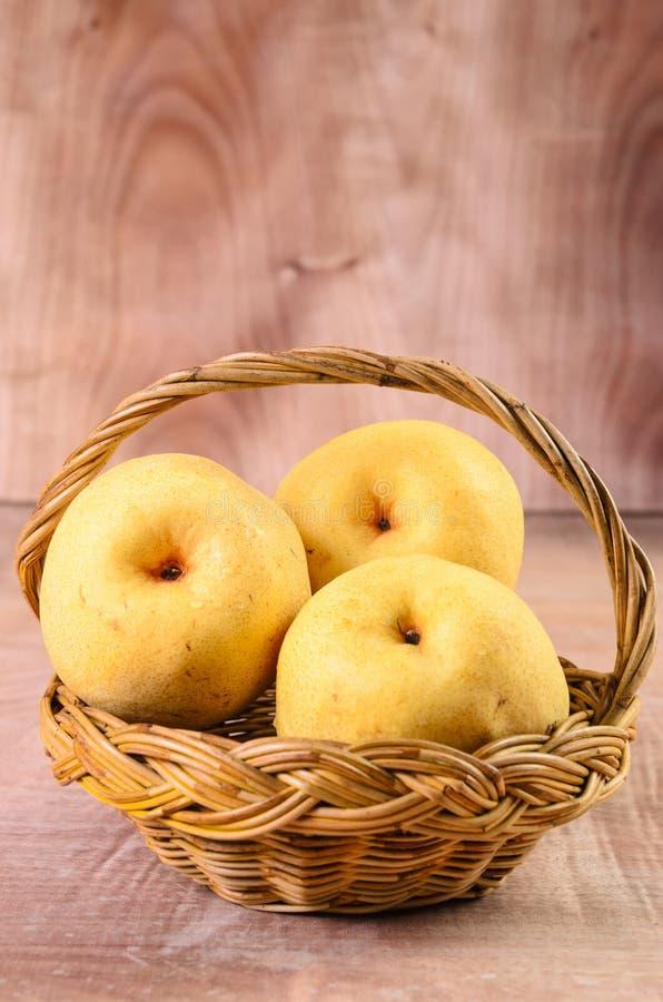 Manzanas en cesta en un fondo de madera foto de archivo