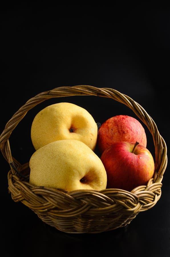 Manzanas en cesta en un fondo negro fotografía de archivo