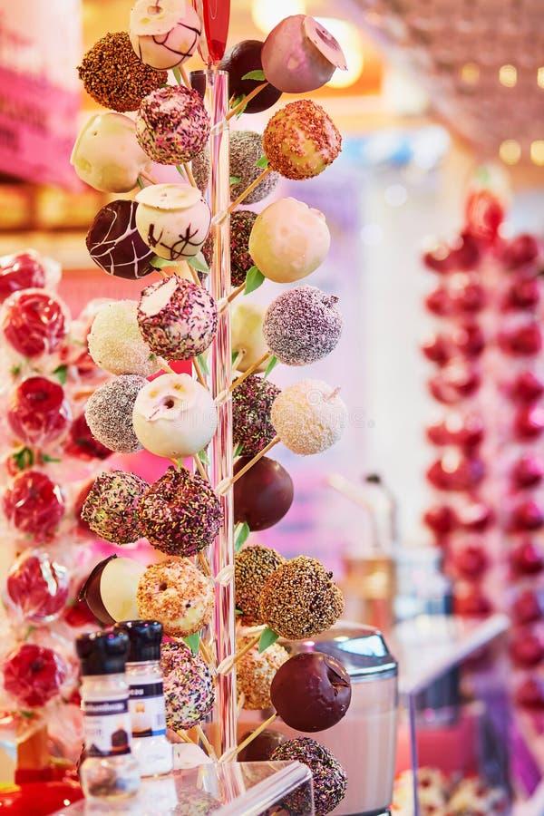 Manzanas en la formación de hielo del chocolate en mercado parisiense de la Navidad fotos de archivo