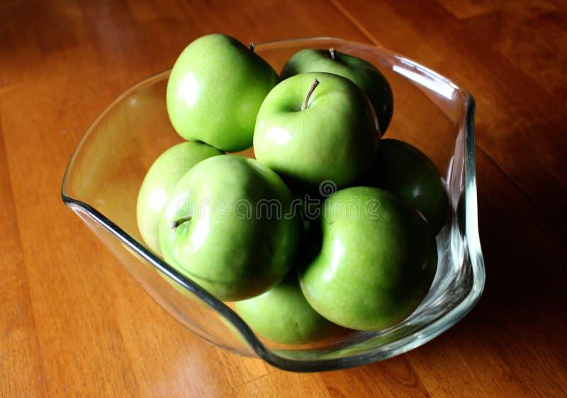 Manzanas en un cuenco decorativo en una tabla de madera imágenes de archivo libres de regalías