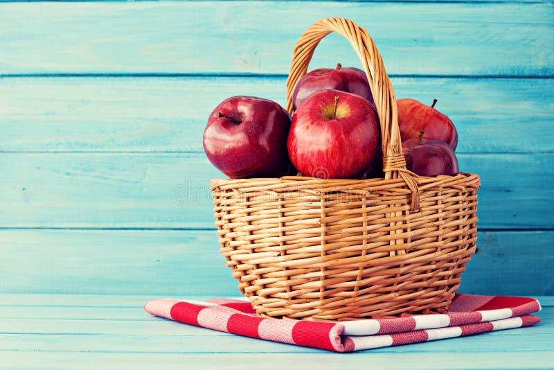 Manzanas en una cesta sobre la madera de la turquesa imágenes de archivo libres de regalías