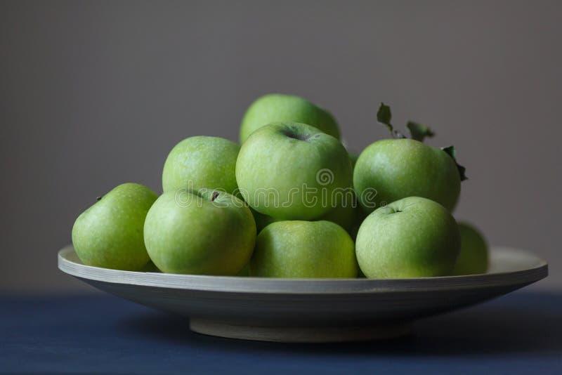 Manzanas frescas verdes en un florero de madera redondo foto de archivo