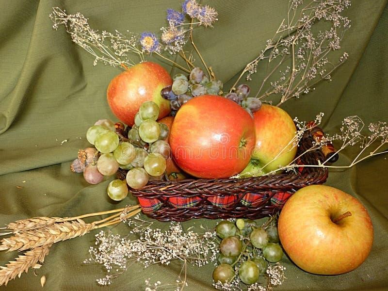Manzanas maduras con las uvas en una cesta imagen de archivo