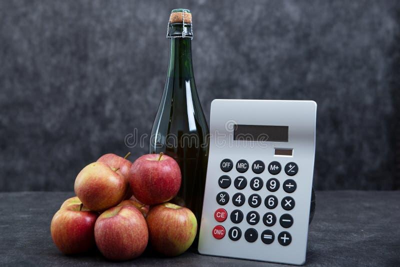 Manzanas orgánicas, botella de sidra y calculadora, concepto costoso foto de archivo libre de regalías