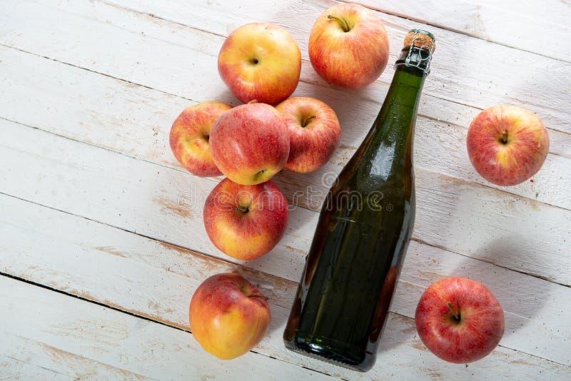 Manzanas orgánicas con una botella de sidra en la tabla de madera blanca fotos de archivo