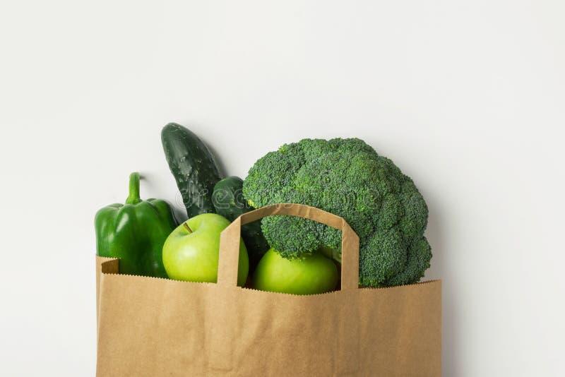 Manzanas orgánicas crudas verdes de los paprikas de los pepinos del bróculi de las frutas de las verduras en bolso de ultramarino foto de archivo libre de regalías