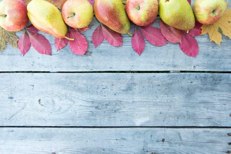 Manzanas, peras y hojas de otoño en fondo de madera CCB del otoño foto de archivo