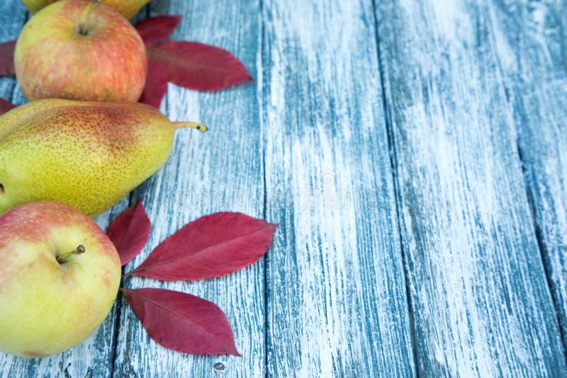 Manzanas, peras y hojas de otoño en fondo de madera CCB del otoño fotos de archivo