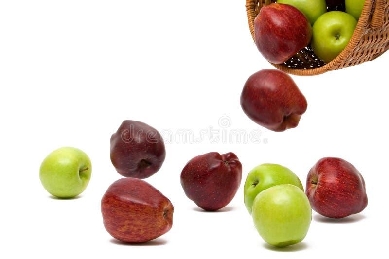 Manzanas que caen de una cesta fotos de archivo