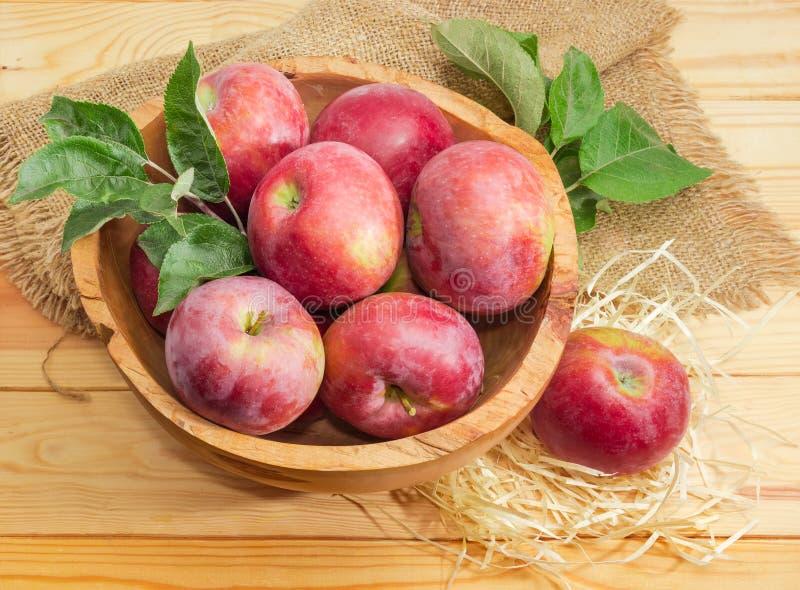 Manzanas rojas con las ramitas en el cuenco de fruta de madera del vintage imagen de archivo
