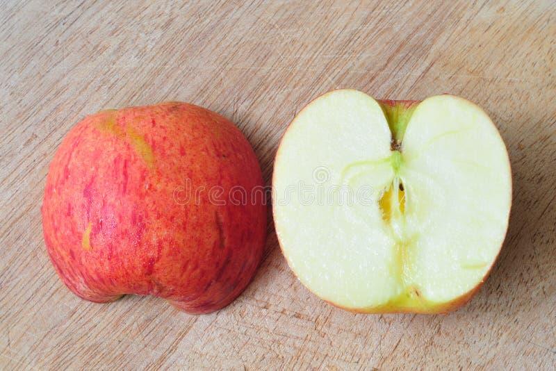 Manzanas rojas de la diapositiva en la tabla de madera. imagenes de archivo