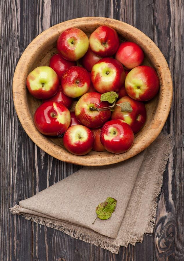 Manzanas rojas en cuenco de madera rústico fotos de archivo