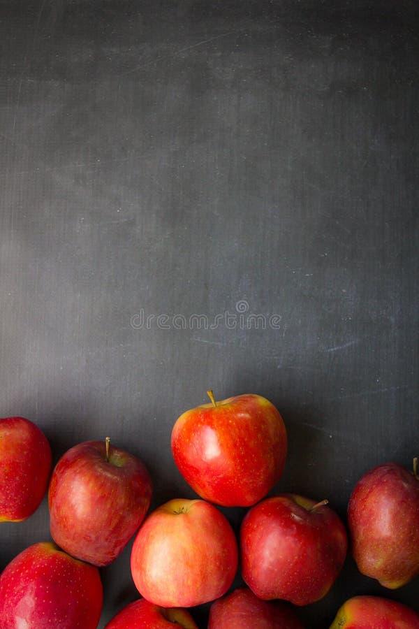 Manzanas rojas en tablero negro imagenes de archivo