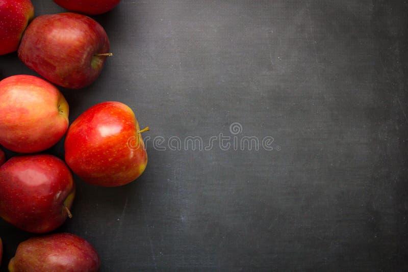 Manzanas rojas en tablero negro imagen de archivo libre de regalías