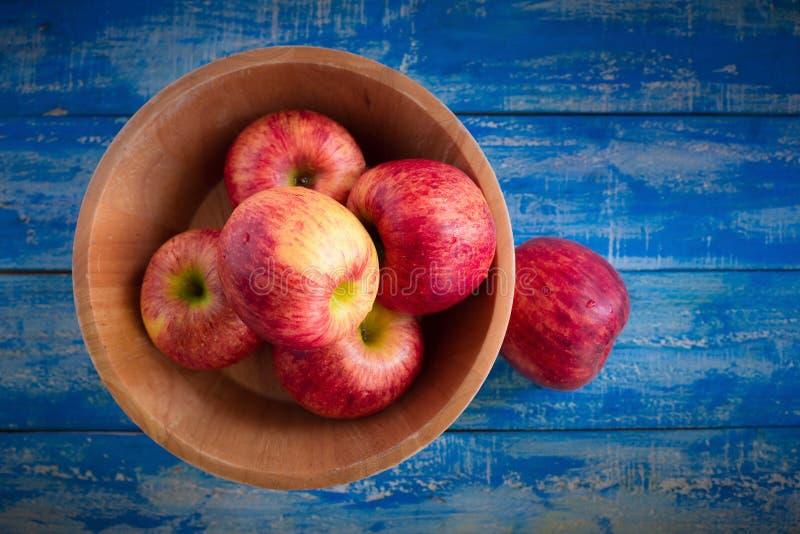 Manzanas rojas en un cuenco de madera en un fondo de madera azul fotografía de archivo libre de regalías