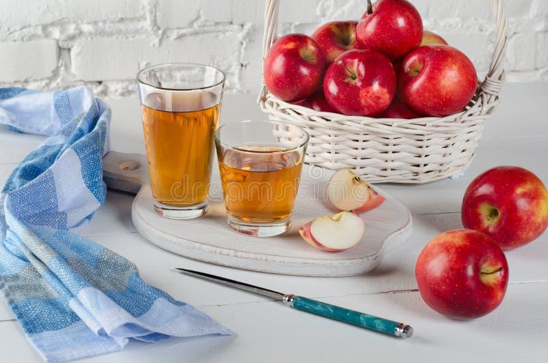 Manzanas rojas, jugo en vidrios, servilleta azul y un cuchillo en la tabla blanca imagen de archivo libre de regalías