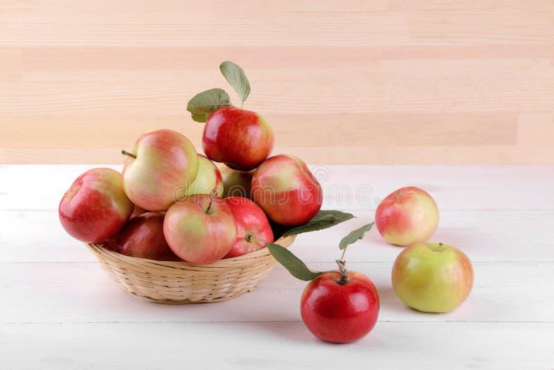 manzanas rojas maduras con las hojas en una cesta en una tabla de madera blanca y en un fondo de la madera natural imagenes de archivo
