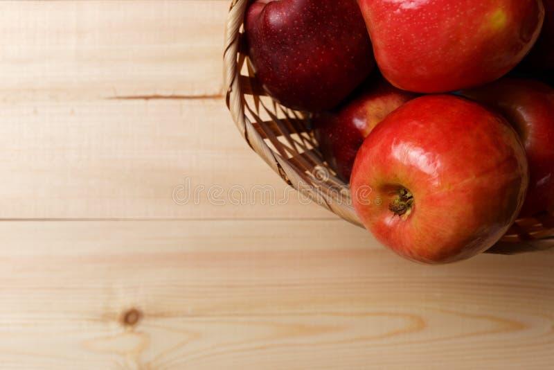 Manzanas rojas maduras en una cesta en un fondo de madera brillante fotografía de archivo