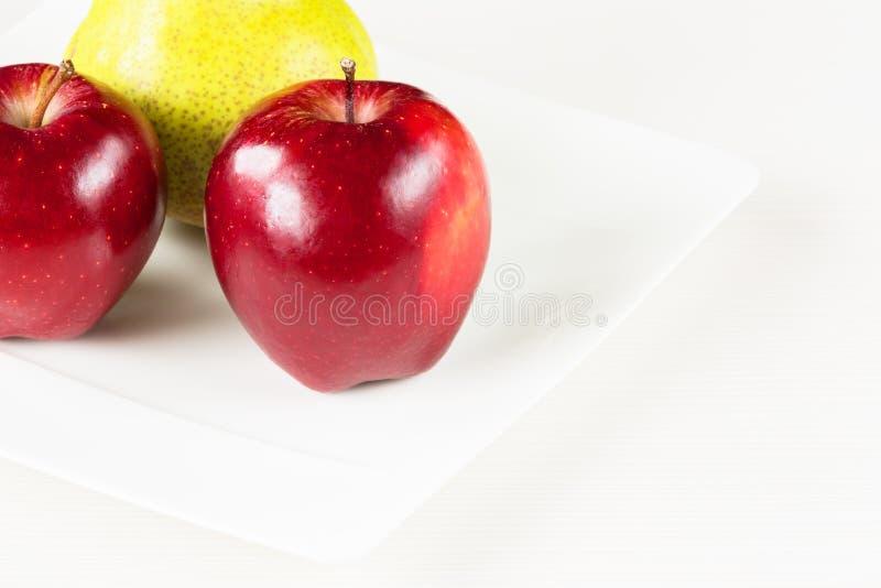 Manzanas rojas, pera verde en la placa blanca en el fondo de madera blanco fotografía de archivo libre de regalías