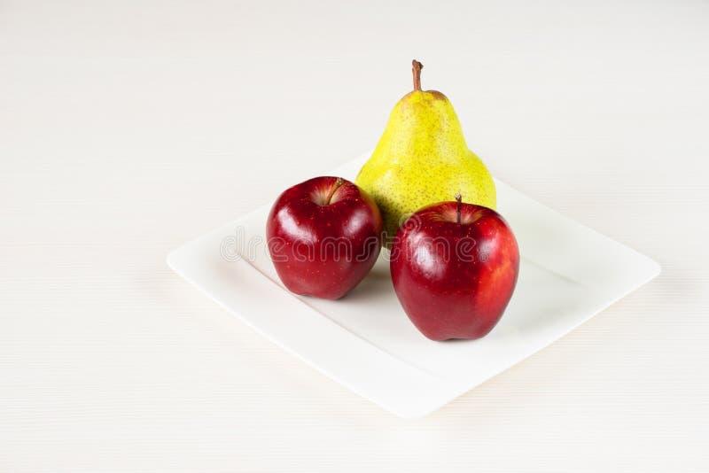 Manzanas rojas, pera verde en la placa blanca en el fondo de madera blanco foto de archivo