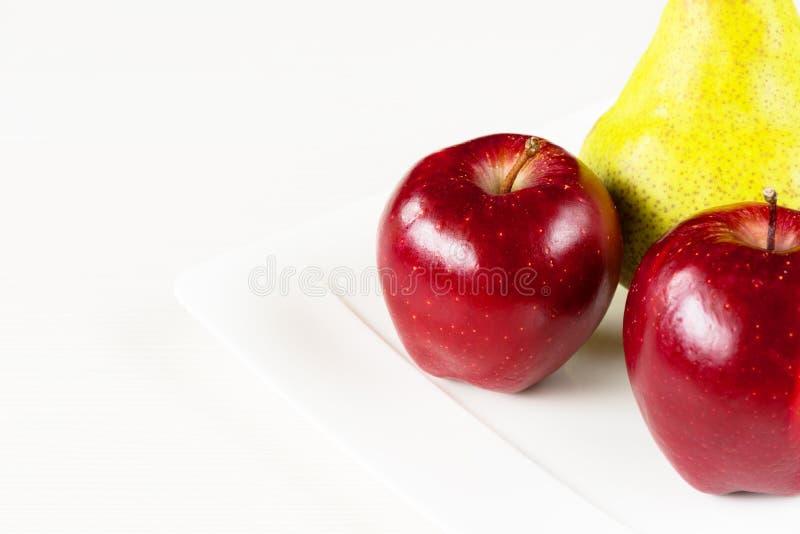 Manzanas rojas, pera verde en la placa blanca en el fondo de madera blanco imagen de archivo