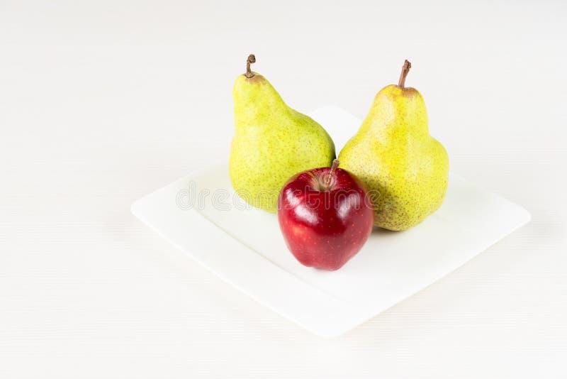 Manzanas rojas, pera verde en la placa blanca en el fondo de madera blanco fotos de archivo