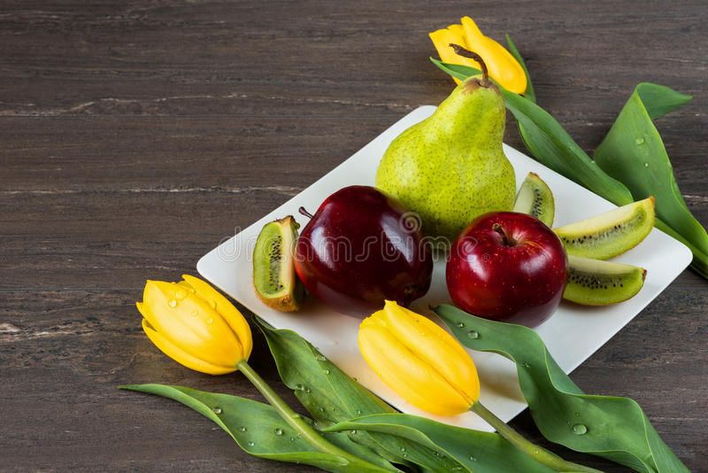 Manzanas rojas, pera verde, kiwi cortado y tulipanes amarillos en la placa blanca en el tablero de madera gris foto de archivo