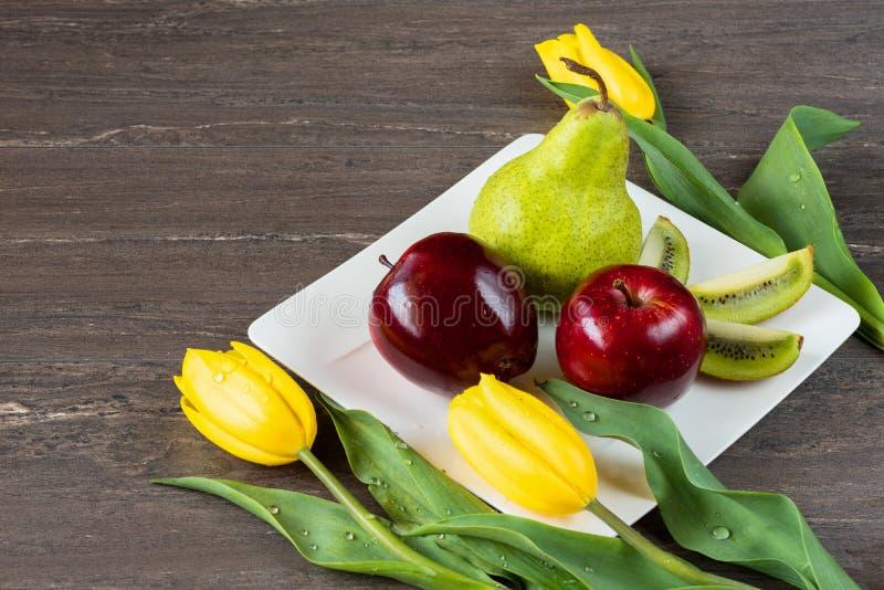 Manzanas rojas, pera verde, kiwi cortado y tulipanes amarillos en la placa blanca en el tablero de madera gris imagen de archivo
