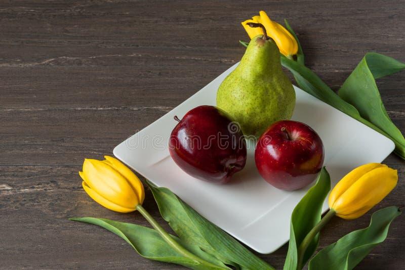 Manzanas rojas, pera verde y tulipanes amarillos en la placa blanca en el tablero de madera gris fotografía de archivo