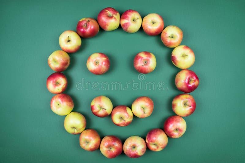 Manzanas rojas y amarillas frescas que forman la cara sonriente en fondo verde imagen de archivo