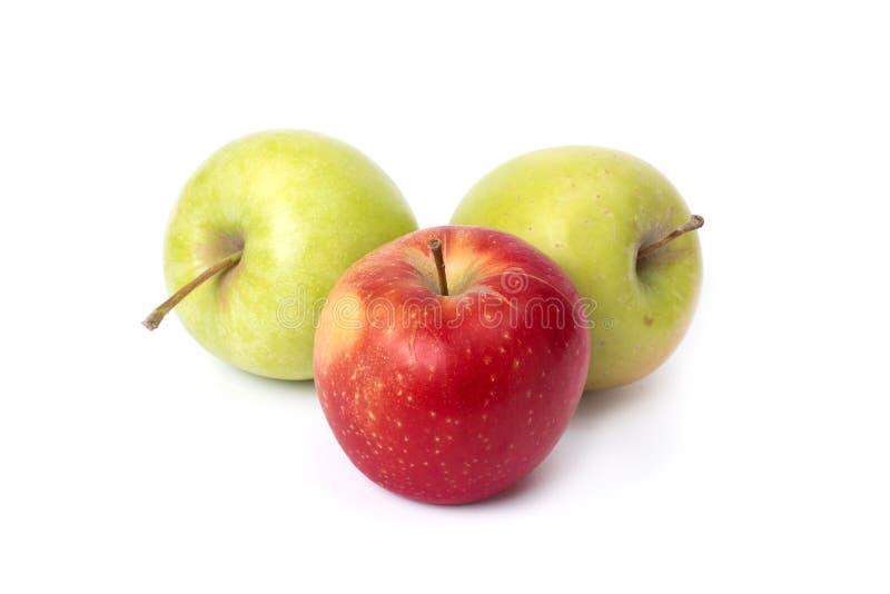 Manzanas rojas y verdes en un fondo blanco Manzanas verdes y rojas jugosas en un fondo aislado Un grupo de ingenio maduro de tres foto de archivo