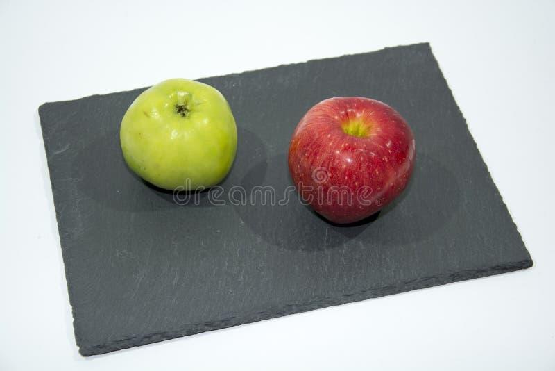 Manzanas rojas y verdes que mienten en un estante de la porción de la pizarra fotografía de archivo libre de regalías