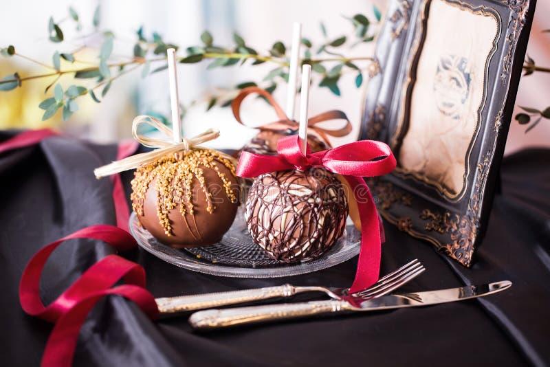 Manzanas sumergidas en chocolate en un palillo fotos de archivo